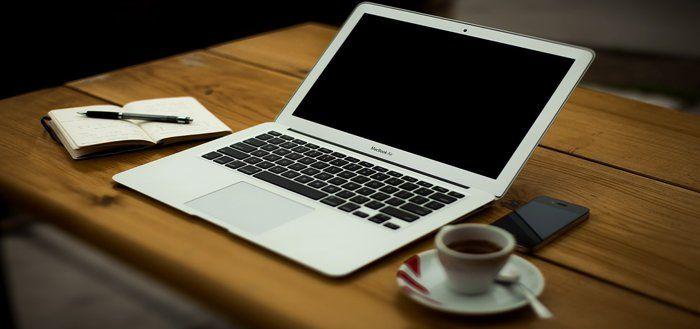 Escritorio con ordenador portátil, smartphone, café y bloc de notas