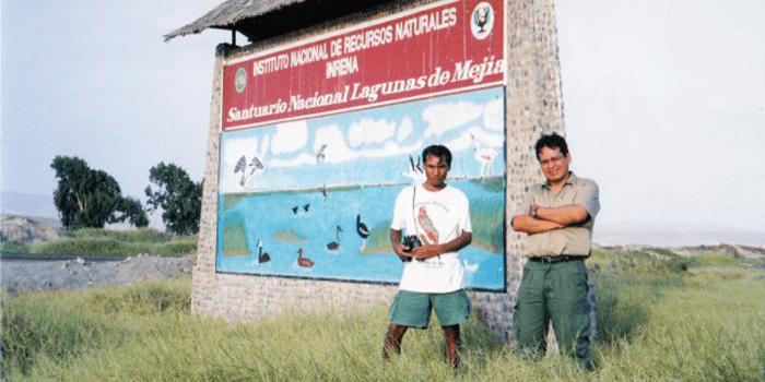 Ernesto, en pie, junto al cartel que anuncia el Santuario Nacional Lagunas de Mejia