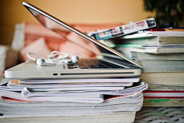 Ordenador encima de un montón de cuadernos